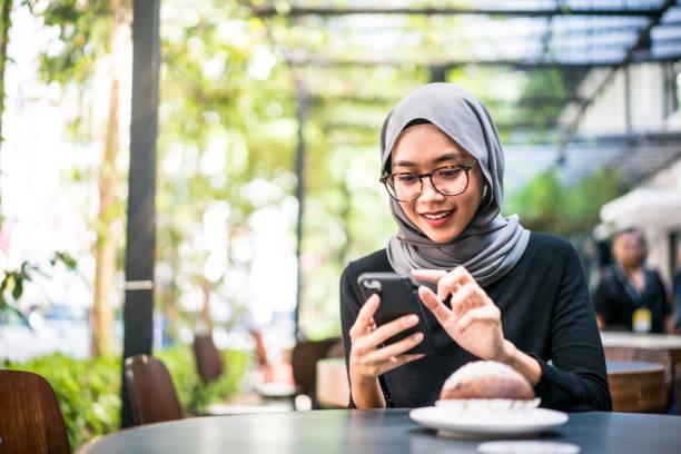 Cheerful Malaysian girl using her smartphone stock photo