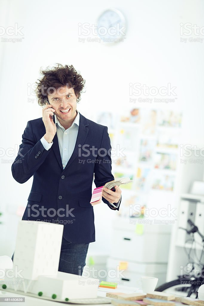 Cheerful male architect on the phone in the office. royalty-free stock photo