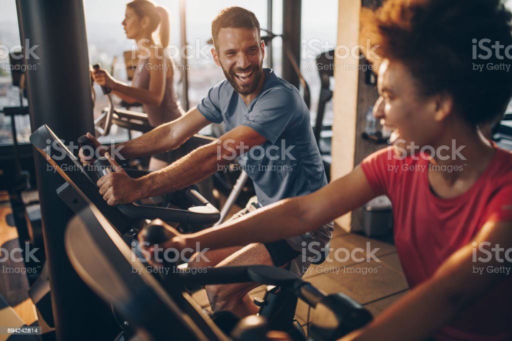 Cheerful male athlete talking to his friend on spinning training in a health club. stock photo