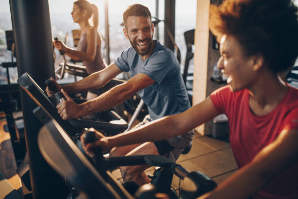 cheerful male athlete talking to his friend on exercising training in a health club. - health club stock photos and pictures