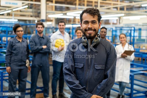 Cheerful male blue collar worker wearing protective ear muffs on neck smiling at camera and group of employees standing behind - Industrial concepts