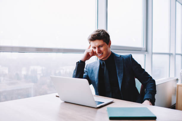 Cheerful male businessman in formal wear sitting at desktop and watching funny comedy video via multimedia application on modern laptop device, smiling male entrepreneur reading positive news stock photo