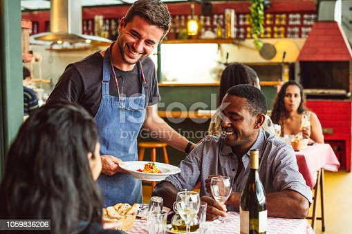 Young cook standing by diners in small eatery, placing meal on table, customers looking at food and drinking wine