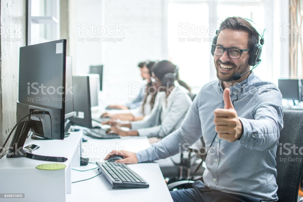 Cheerful male customer service operator showing thumbs up in office. stock photo