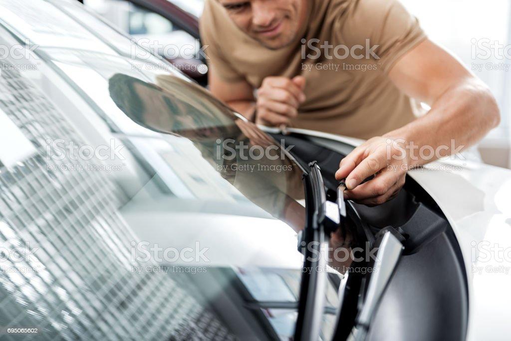 Cheerful male examining technical equipment of car – zdjęcie
