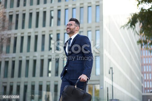 istock Cheerful male executive manager enjoying sunny spring weather strolling outdoors passing copy space area for your advertising, smiling owner of trading company satisfied with successful project 904410038