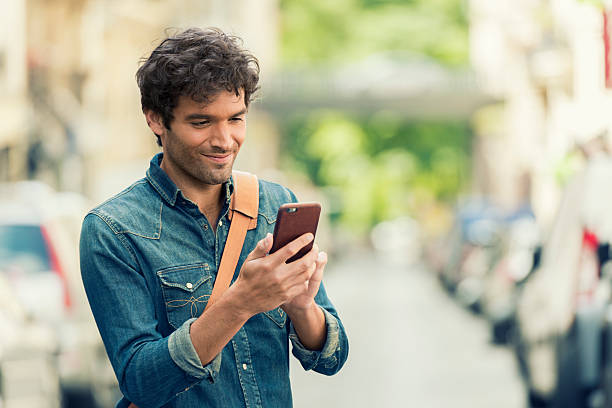 cheerful male in the street texting on mobile phone. - application mobile photos et images de collection