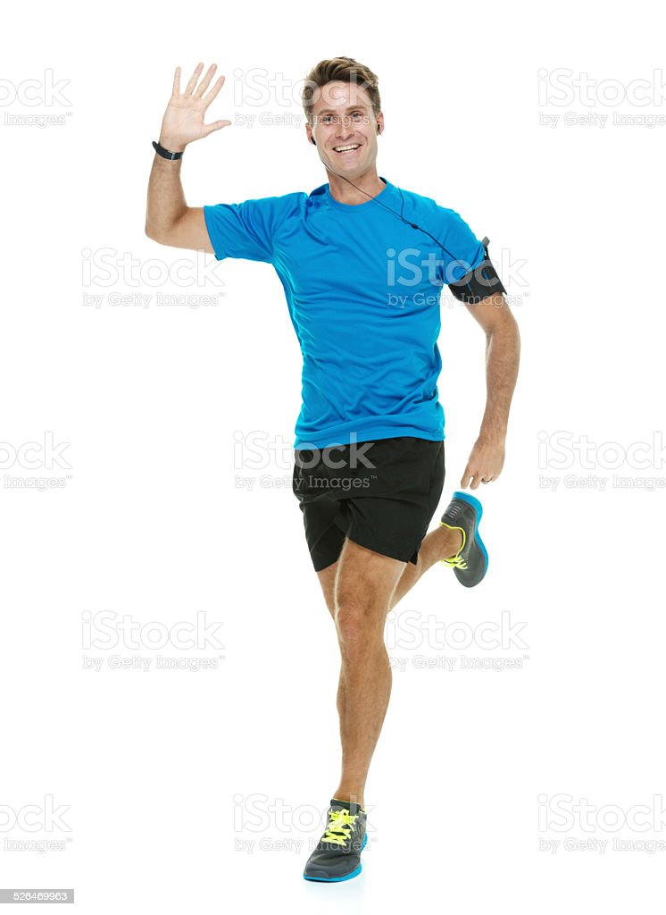 Cheerful male runner running & waving hand stock photo