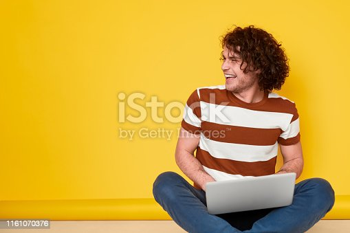 Excited young man in casual outfit laughing and looking away while doing homework on laptop against yellow background