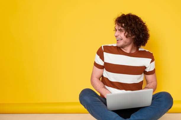 Cheerful male student using laptop Excited young man in casual outfit laughing and looking away while doing homework on laptop against yellow background yeah right stock pictures, royalty-free photos & images
