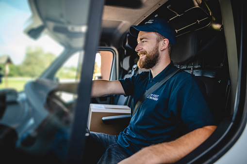 Smiling young bearded delivery expert sitting in driver's seat of van and ready to begin transporting packages to destinations.