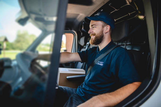 Cheerful Male Uniformed Gig Delivery Driver Sitting in Van stock photo