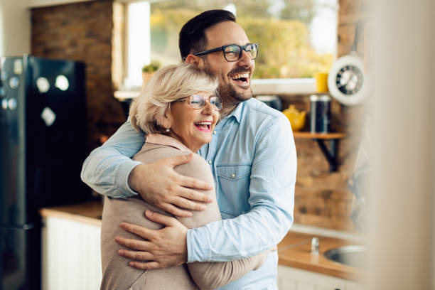 Cheerful man and his mature mother embracing in the kitchen. stock photo