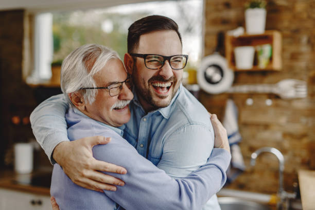 Cheerful man and his senior father embracing while greeting in the kitchen. Happy mature man having fun while embracing with his adult son who came to visit him. father stock pictures, royalty-free photos & images