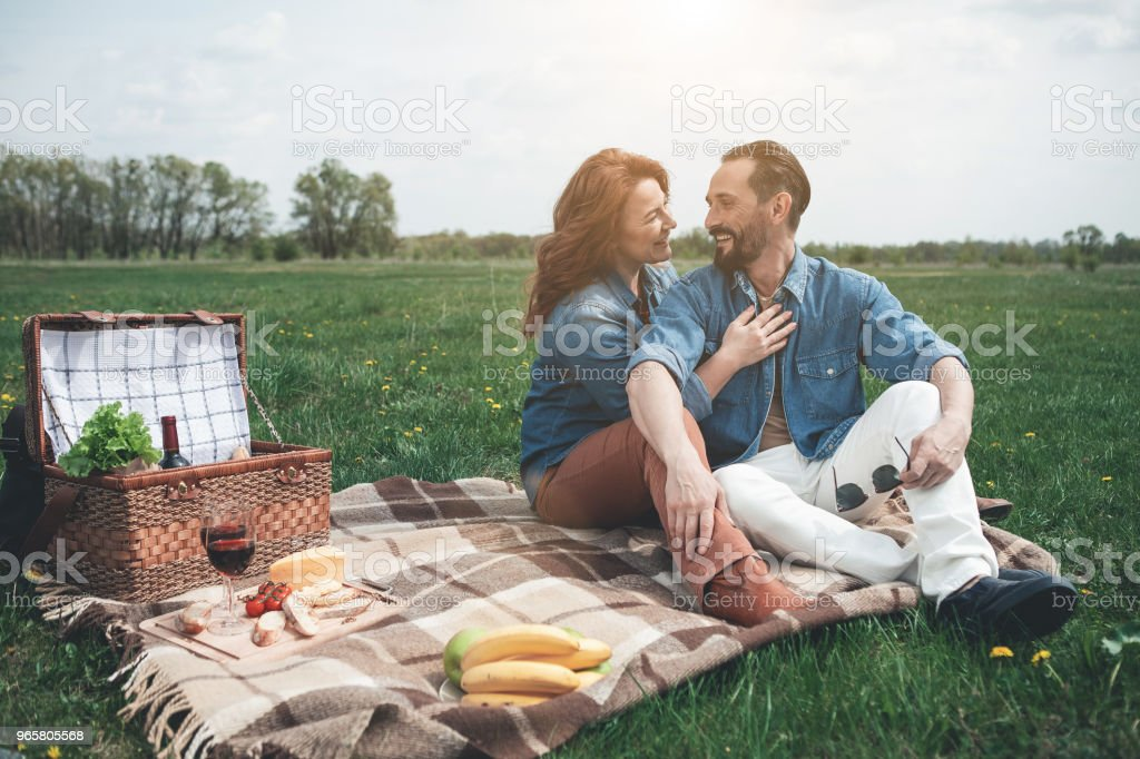 Cheerful man and woman relaxing on grass field - Royalty-free Abraçar Foto de stock