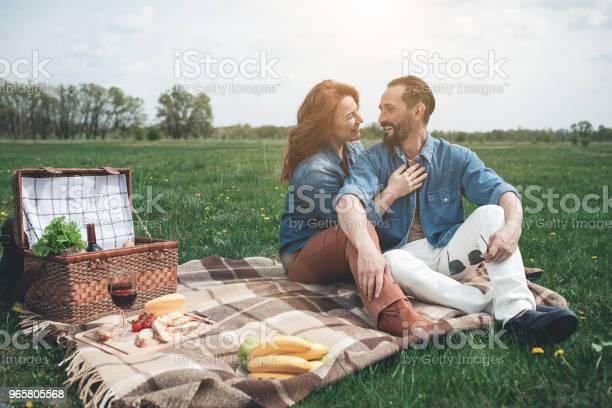 Cheerful Man And Woman Relaxing On Grass Field - Fotografias de stock e mais imagens de Abraçar