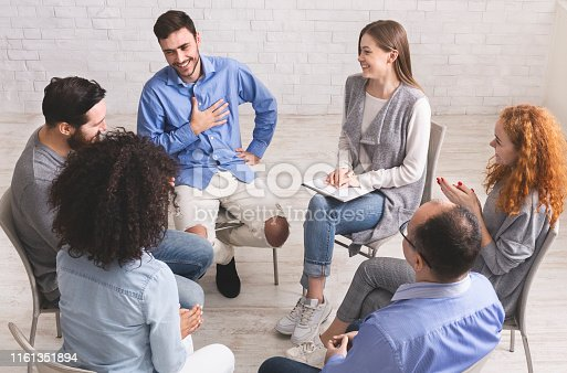 istock Cheerful man appreciates support of people at rehab group meeting 1161351894