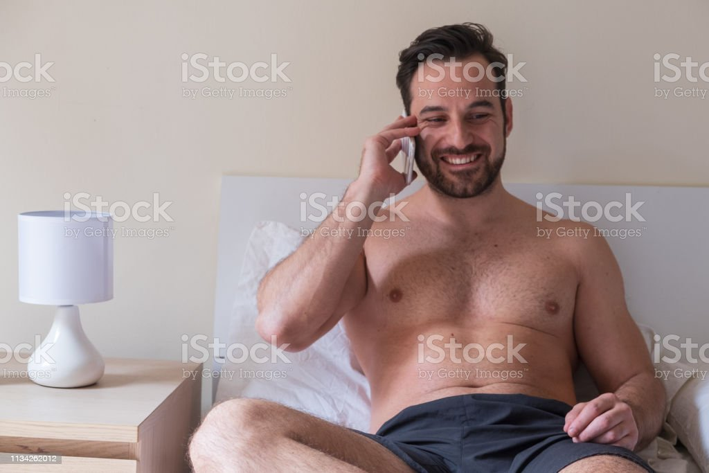 Cheerful Man Calling Someone Lying In Bed Stock Photo