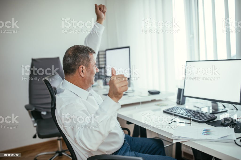 One senior man sitting at the office and celebrating success at work.