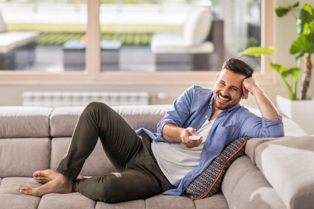 Cheerful man changing channels while relaxing on sofa at home. Young cheerful man relaxing on sofa in the living room and changing channels with remote control. changing channels stock pictures, royalty-free photos & images