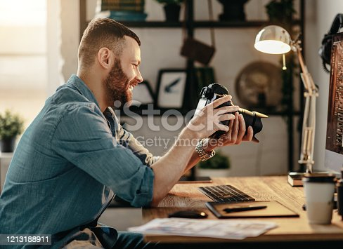 Side view of positive young male photographer checking pictures on photo camera and laughing while working at table at home