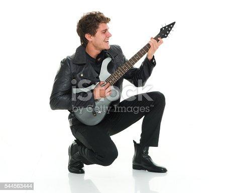 istock Cheerful man crouching and playing guitar 544563444