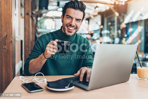 Smiling young man drinking coffee and using laptop in cafe