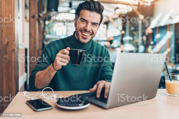 Cheerful man drinking coffee and using laptop in cafe picture id1141961399?b=1&k=6&m=1141961399&s=612x612&h=xgtdw9nn5h6nagmlno5jxovfaoxtlxxm5 gfvzqbxc4=