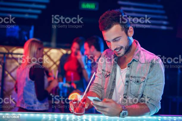 Cheerful man having cocktail while text messaging in nightclub picture id874010808?b=1&k=6&m=874010808&s=612x612&h=coenlb2sgelkvpalx0pyhedrgzqsmuvylp714exo29q=