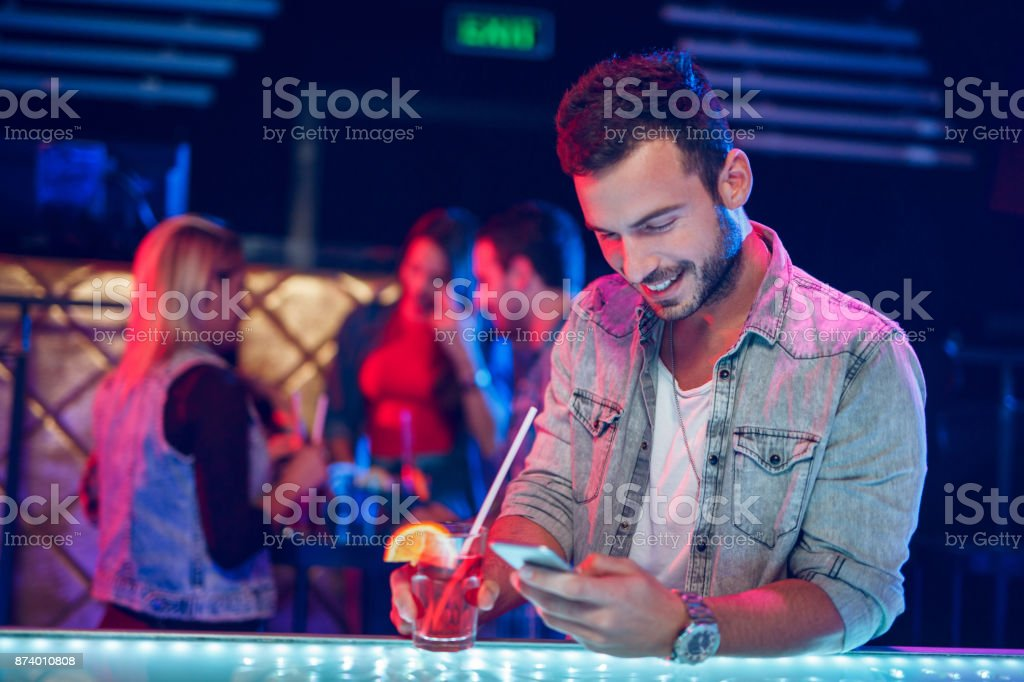 Cheerful man having cocktail while text messaging in nightclub stock photo