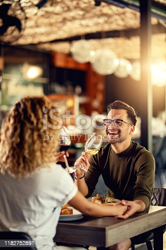 Young couple drinking wine and having fun during lunch in a bar. Focus is on man.