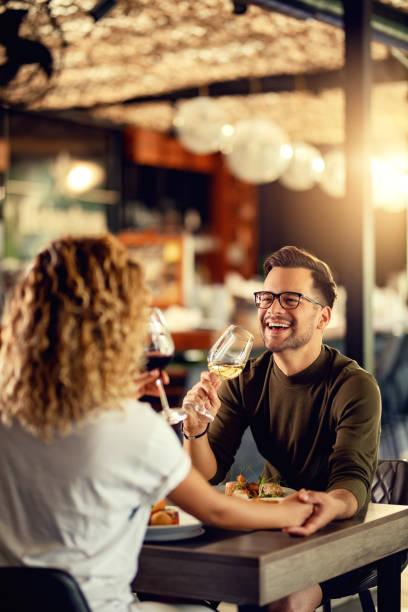 bir restoranda kız arkadaşı ile şarap içerken neşeli adam eğleniyor. - bar i̇çkili mekan stok fotoğraflar ve resimler