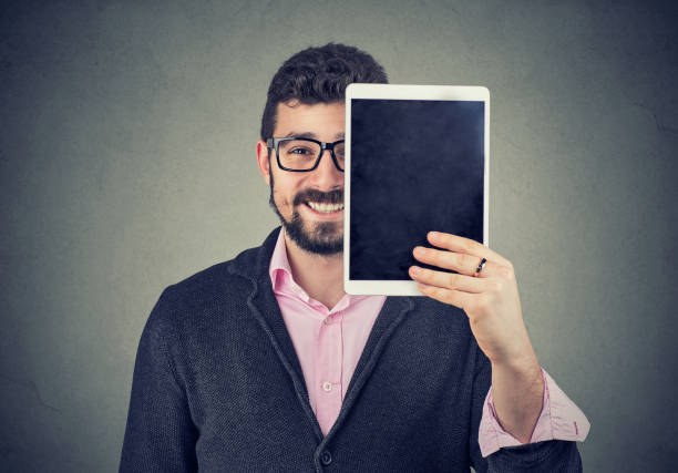 Cheerful man holding a tablet in front of his face stock photo