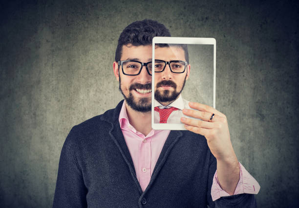 Cheerful man holding a tablet with serious self portrait on screen stock photo