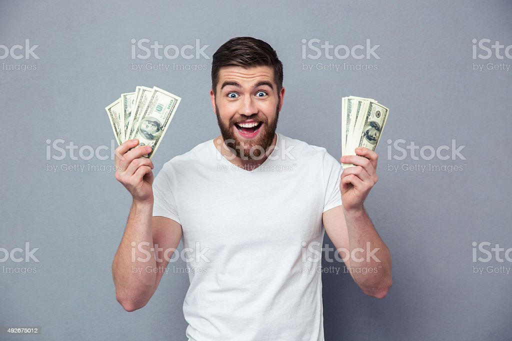 Cheerful man holding dollar bills stock photo