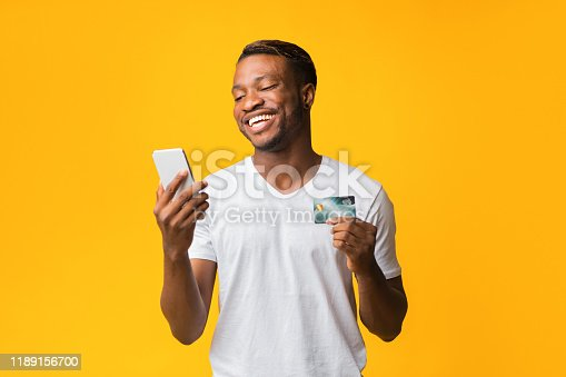 1173546354 istock photo Cheerful Man Holding Phone And Credit Card Standing In Studio 1189156700