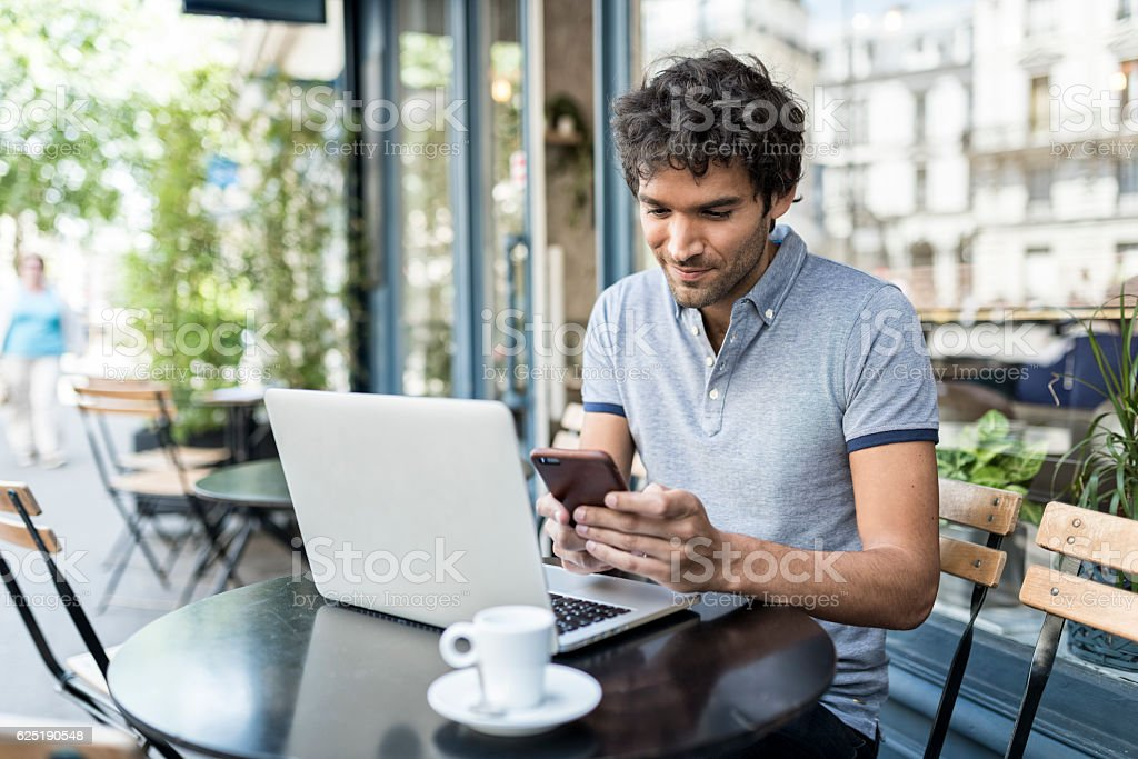 Cheerful man in cafe terrace texting on smartphone. stock photo