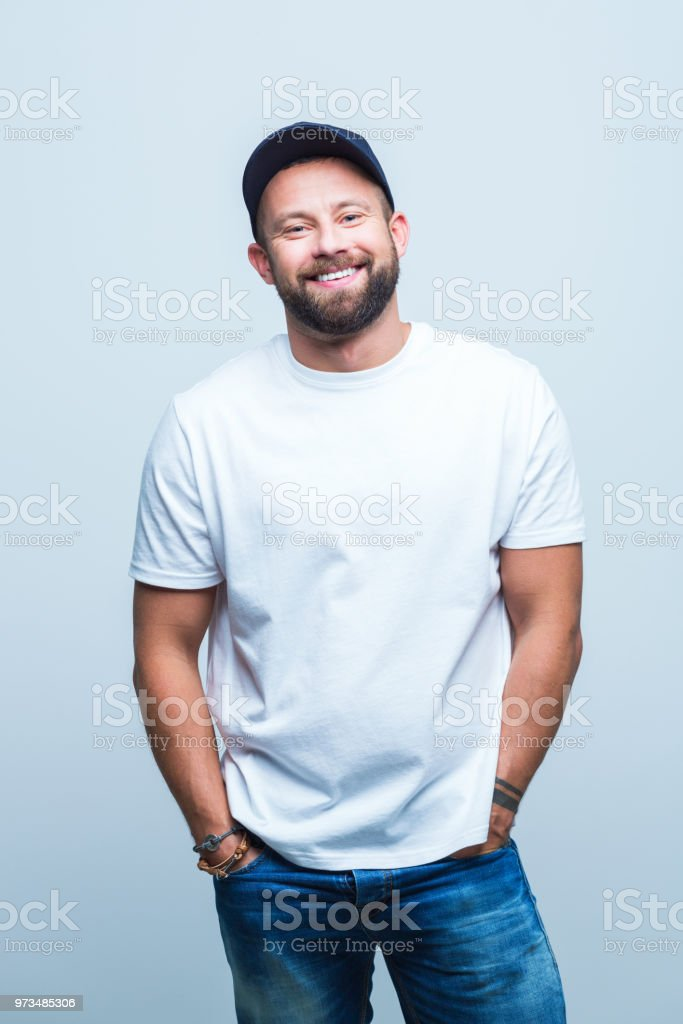 Cheerful man is casuals Portrait of cheerful young man is casuals standing on white background with hands in pocket. Adult Stock Photo
