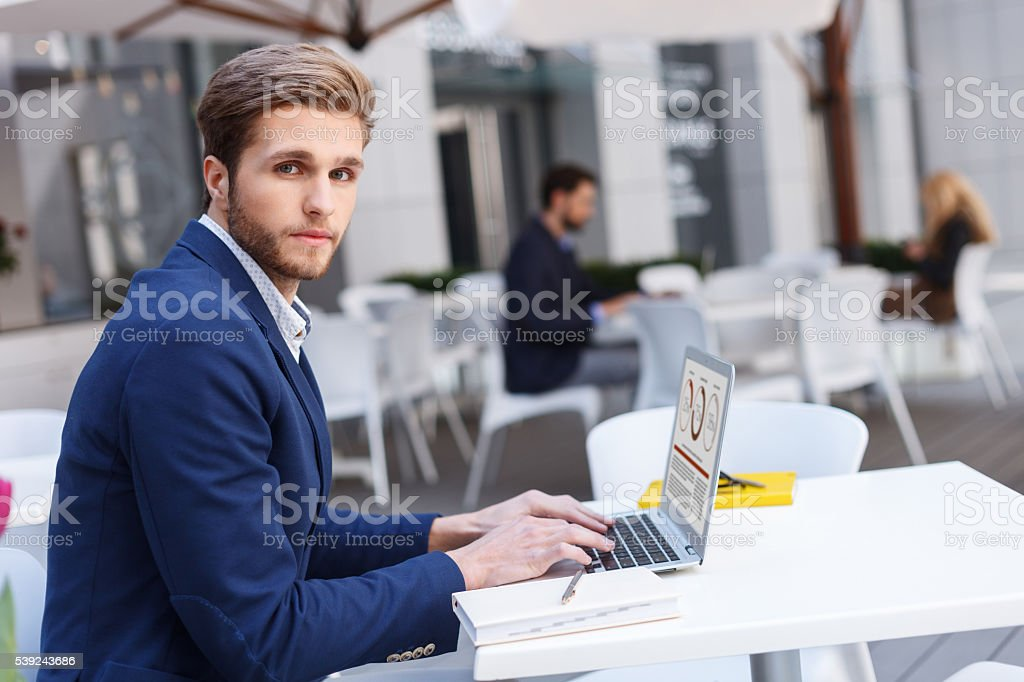 Cheerful man is working on computer in restaurant royalty-free stock photo