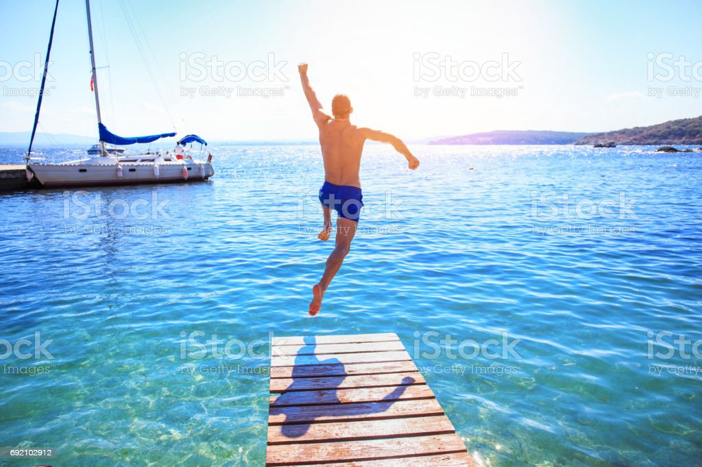 Cheerful man jumping into water stock photo