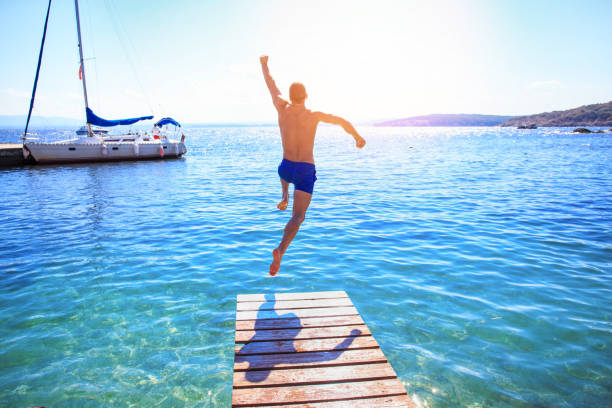cheerful man jumping into water - water day stock photos and pictures