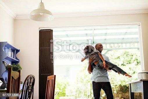 istock Cheerful man lifting boy at home 627011396
