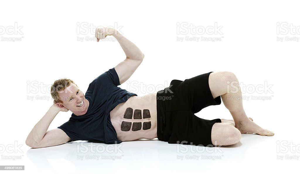 Cheerful man lying on ground with fake six pack royalty-free stock photo