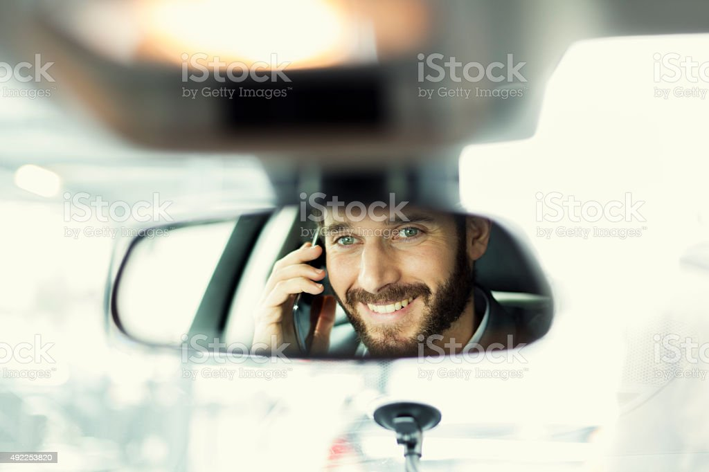 Handsome man smiling on cell phone in the car in the interior mirror