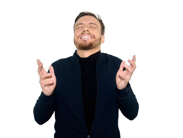 O homem alegre abre os dentes e os punhos, se alegra seu triunfo, eram expressão muito feliz, olhos próximos, isolados no fundo branco. Povos, sucesso, conceito da língua de corpo - foto de acervo