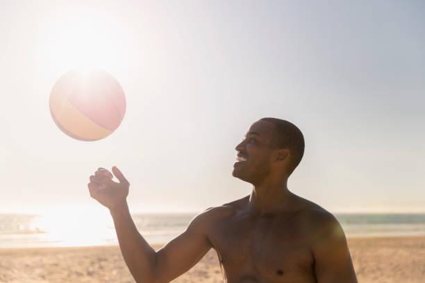 Fröhlicher Mann spielt mit Fußball am Strand – Foto