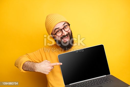 istock Cheerful man pointing at laptop 1094980754
