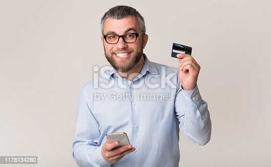 1173546354 istock photo Cheerful man recommending credit card, holding cellphone 1178134260