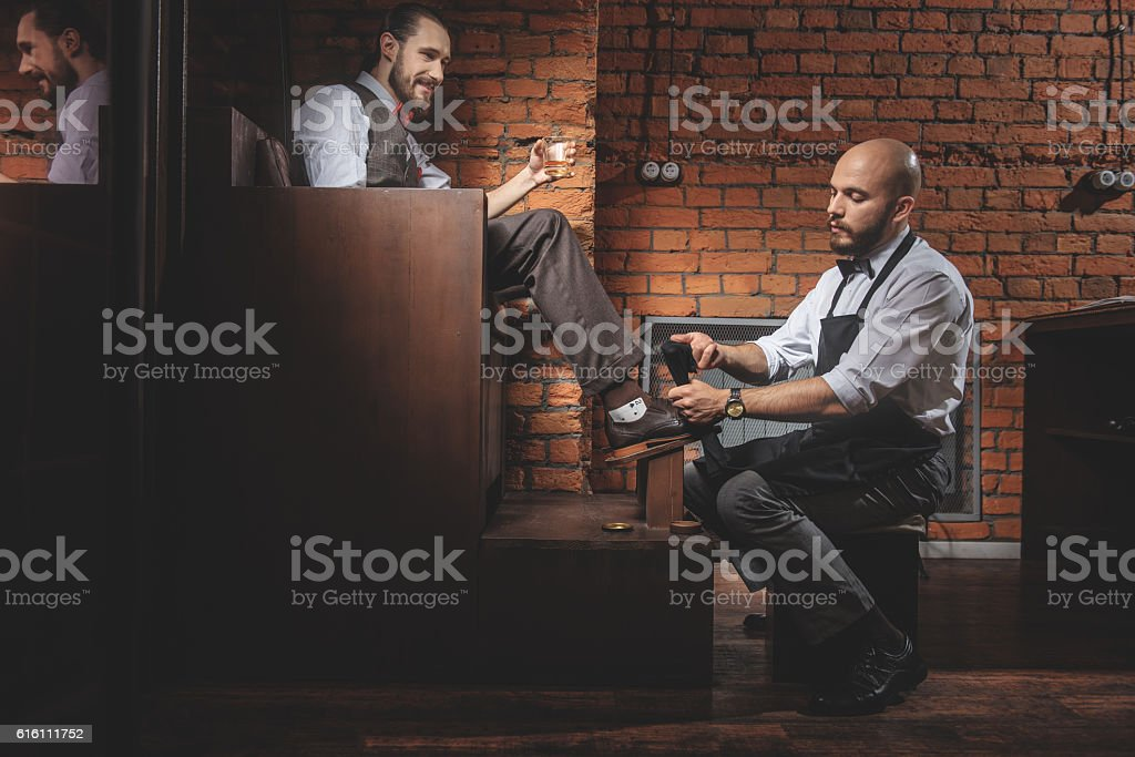 cheerful man resting in front of shoeshiner indoors stock photo