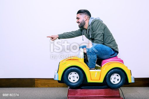 Side view of adult playful man sitting in small kids car and having fun pointing forward.
